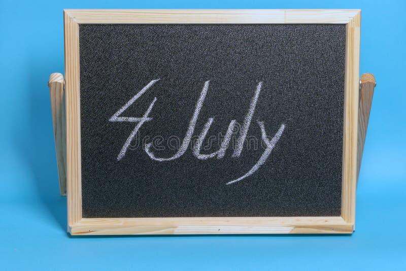 Le tableau noir avec le mot a marqué à la craie le 4ème juillet sur le fond bleu photo libre de droits