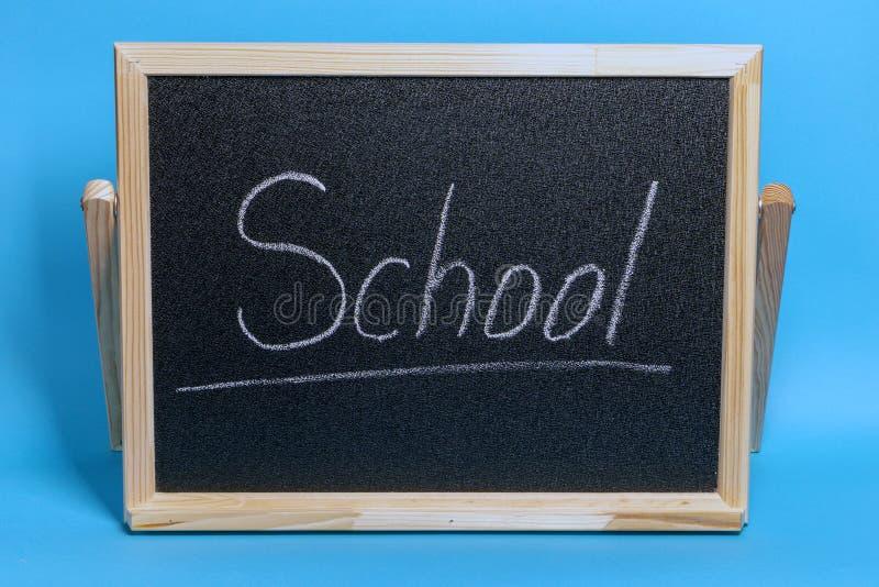 Le tableau noir avec le mot a marqué l'école à la craie sur le fond bleu photos stock