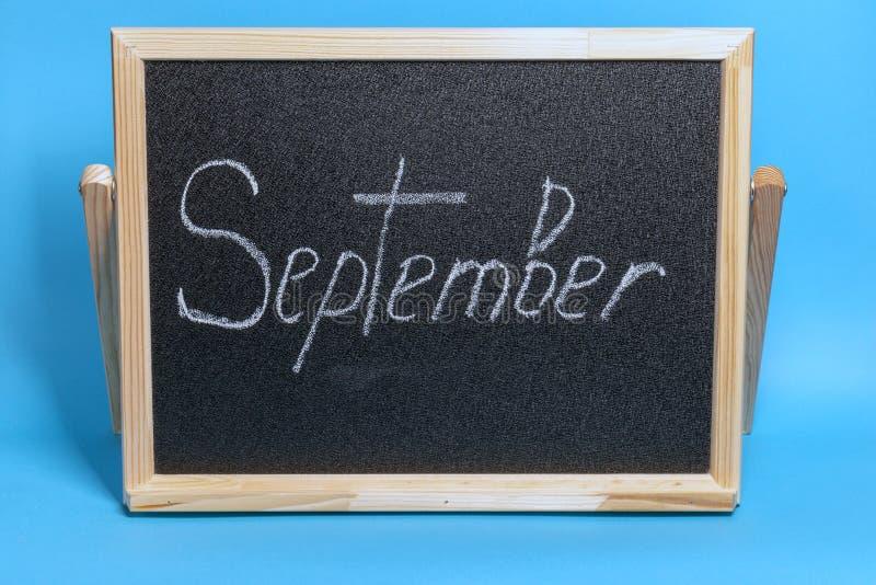 Le tableau noir avec le mot a marqué septembre à la craie sur le fond bleu image libre de droits