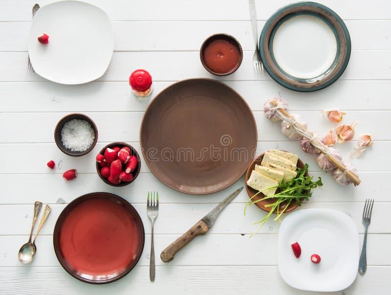 Le Tableau a servi à quatre avec les plats, le radis et l'ail vides photo stock