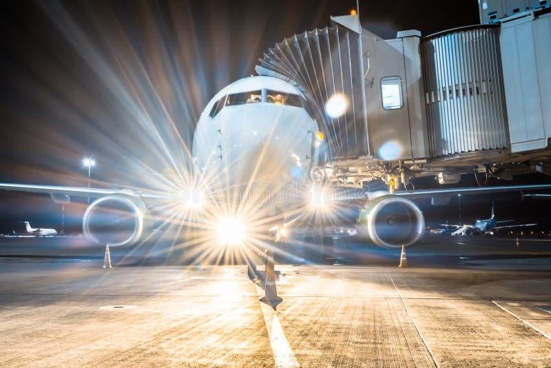 Le tablier d'avions à la passerelle de stationnement à l'aéroport la nuit avec les lumières a tourné le débarquement photo stock