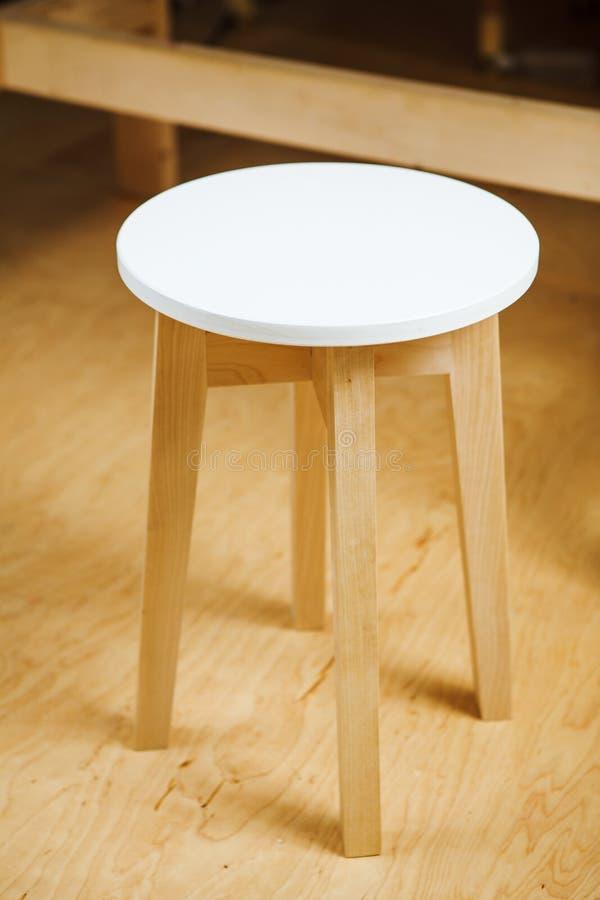 Le tabouret en bois avec le siège rond et les longues jambes se tient sur le plancher de parquet photographie stock libre de droits