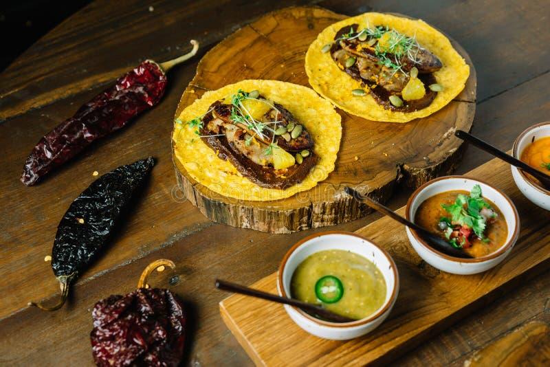 Le Tacos de Foie Gras a servi sur le hachoir en bois avec différentes sauces et le Mexicain a séché le piment image libre de droits