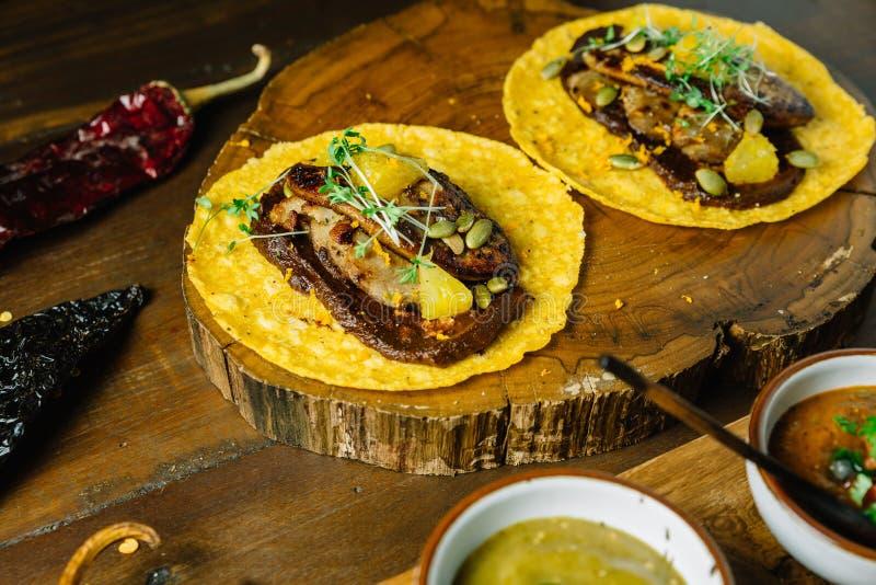 Le Tacos de Foie Gras a servi sur le hachoir en bois avec différentes sauces et le Mexicain a séché le piment image stock