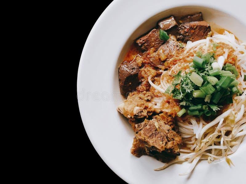 Le tagliatelle di riso con carne di maiale piccante sauce sul nero isolata fotografia stock libera da diritti