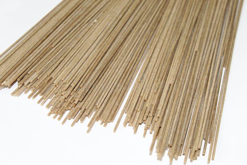Le tagliatelle sottili lunghe marrone chiaro del grano saraceno hanno disposto isolato su fondo bianco immagini stock