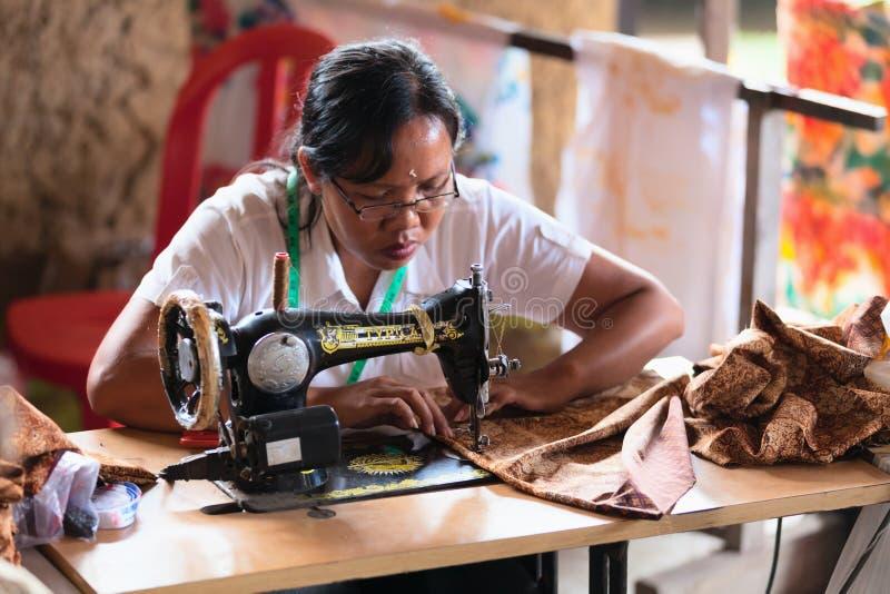 Le tailleur féminin de Balinese cousent sur une machine photo libre de droits