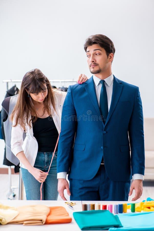 Le tailleur professionnel prenant des mesures pour le costume formel image libre de droits