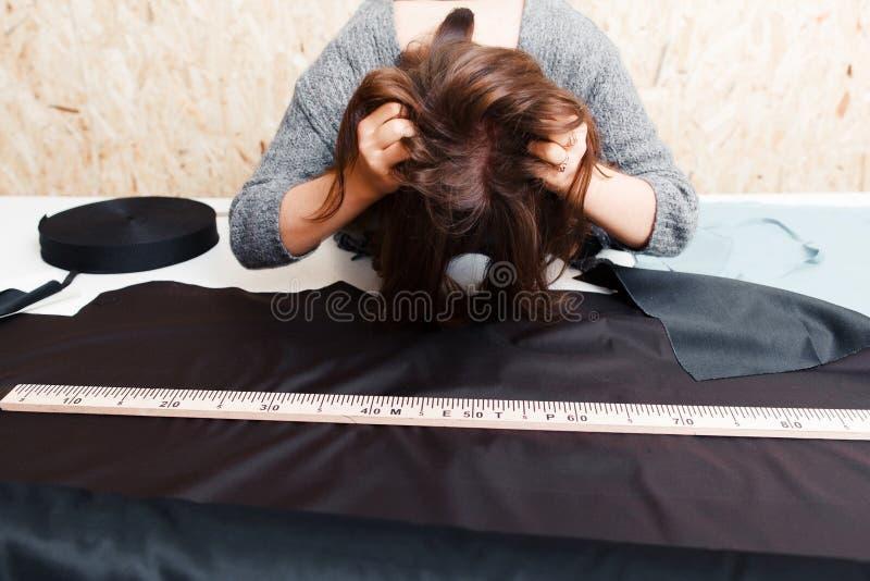 Le tailleur soumis à une contrainte de femme ébouriffent ses cheveux sur le lieu de travail photographie stock libre de droits