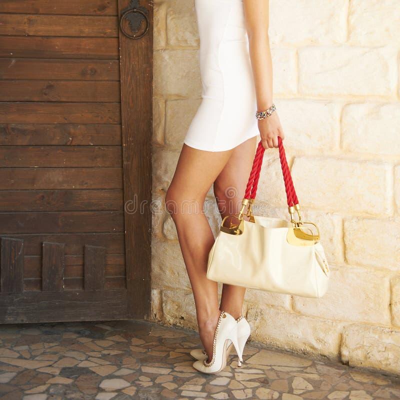 Le talon haut blanc chaussé femelle chausse se tenir dans un sac de mode de main photographie stock