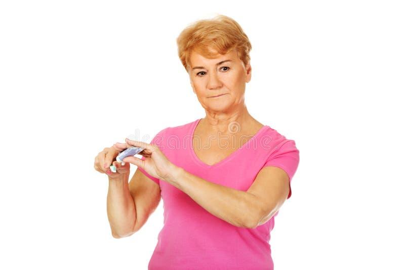 Le tandkräm och tandborsten för hög kvinna hållande arkivfoto