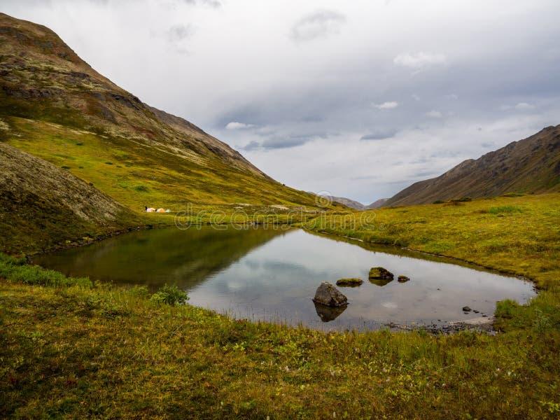 Le Tarn dans la vallée de montagne et l'Autumn Tundra, tentes sur le rivage lointain image libre de droits