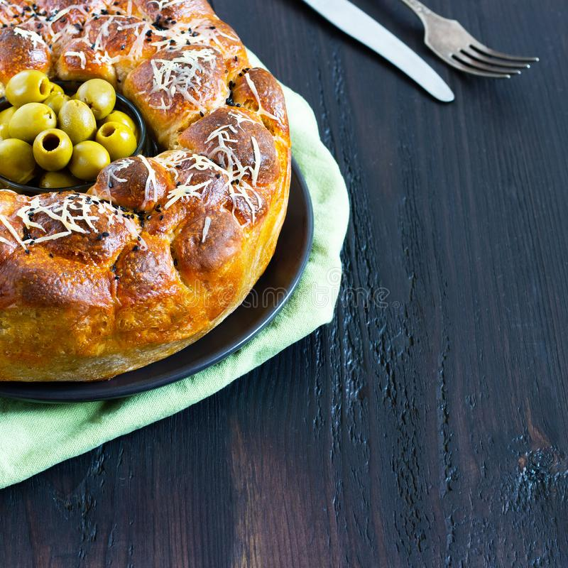 Le tarte savoureux, le baobab rond avec des oives bourrés de petits pains et le fromage, complété avec du fromage râpé et le bol  photographie stock