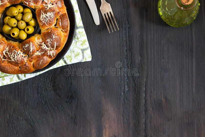 Le tarte savoureux, le baobab rond avec des oives bourrés de petits pains et le fromage, complété avec du fromage râpé et le bol  image libre de droits
