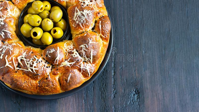 Le tarte savoureux, le baobab rond avec des oives bourrés de petits pains et le fromage, complété avec du fromage râpé et le bol  photographie stock libre de droits