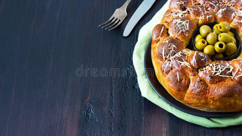 Le tarte savoureux, le baobab rond avec des oives bourrés de petits pains et le fromage, complété avec du fromage râpé et le bol  photos libres de droits