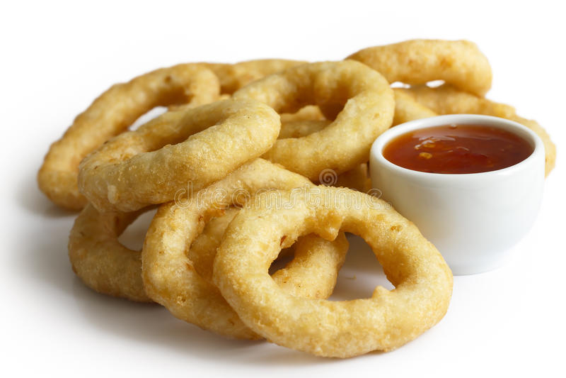Le tas des anneaux cuits à la friteuse d'oignon ou de calamari avec des piments plongent l'isola photos stock