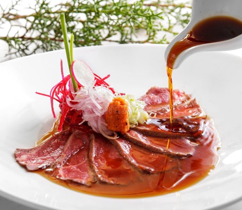 Le tataki japonais de boeuf de cuisine a versé avec la sauce de soja images stock