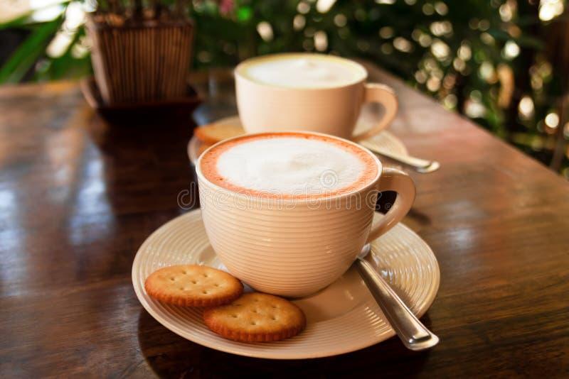 Le tazze delle coppie con il tè tailandese variopinto del latte su una tavola di legno fotografie stock