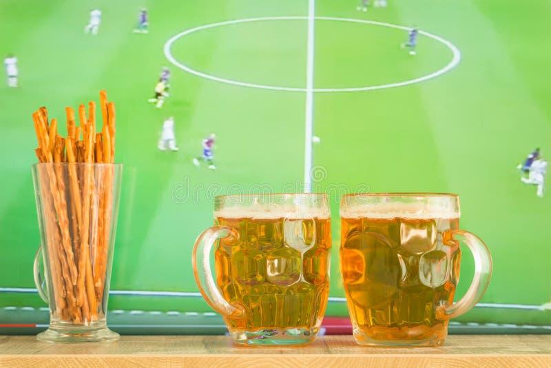 Le tazze di birra sui precedenti della TV abbinano immagini stock