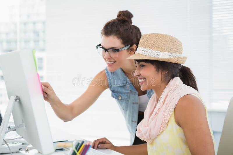 Le teamwork som pekar datoren på skrivbordet royaltyfri fotografi