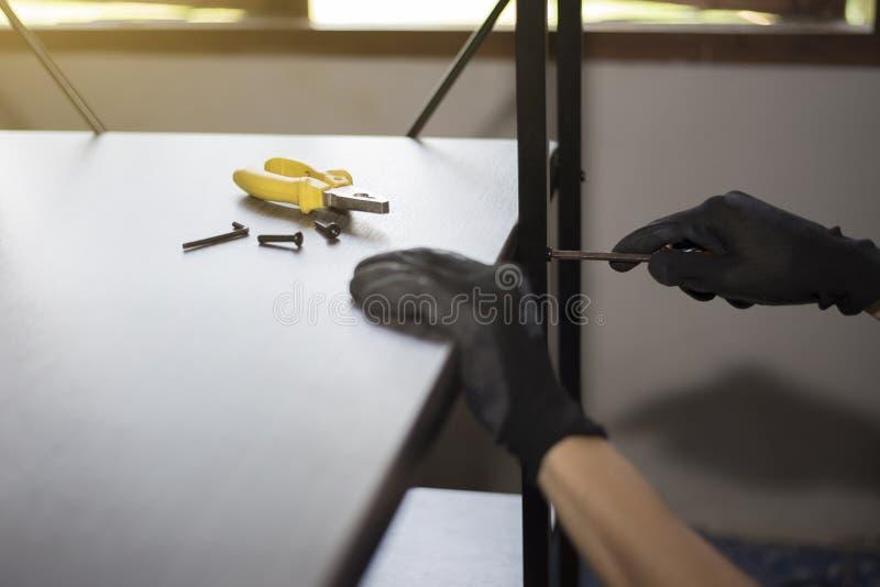 Le technicien de meubles travaille pour assembler des meubles photos stock