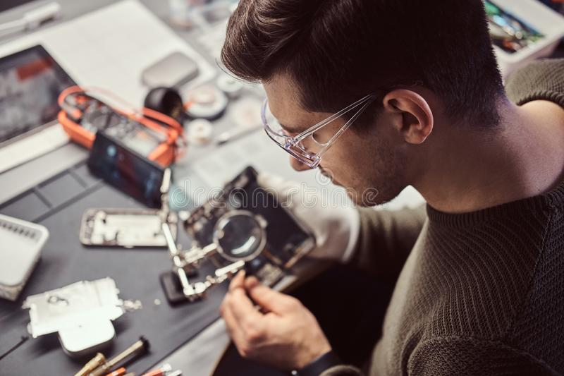 Le technicien réparant un smartphone endommagé dans l'atelier électronique image libre de droits