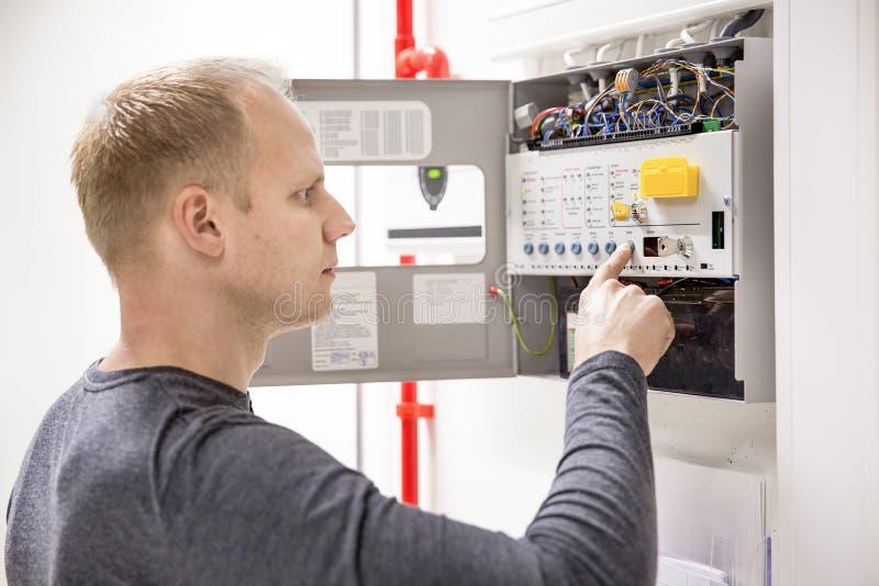 Le technicien vérifie le panneau du feu au centre de traitement des données photo libre de droits