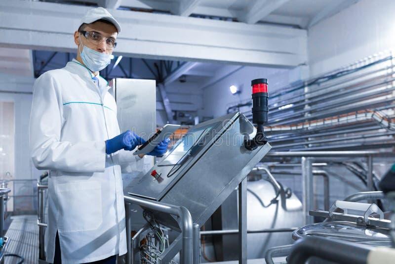 Le technologue se tient avec un comprimé près de l'écran numérique à l'installation laitière images stock