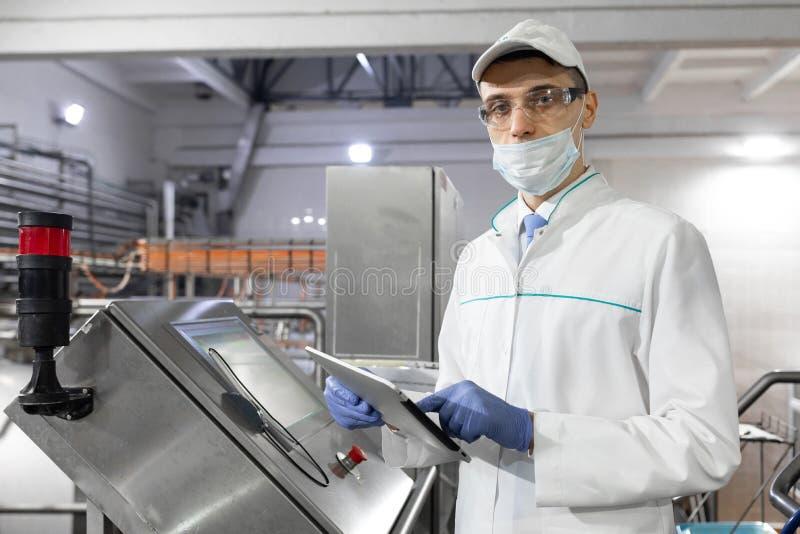 Le technologue se tient avec un comprimé près de l'écran numérique à l'installation laitière image libre de droits
