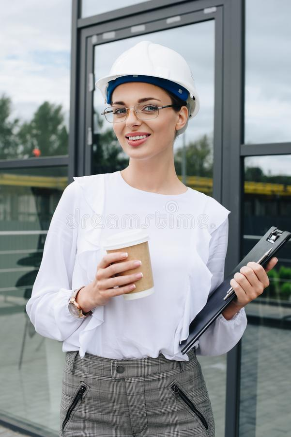 Le teknikern i hardhat, hållande clpboard och pappers- kopp, medan se royaltyfri fotografi