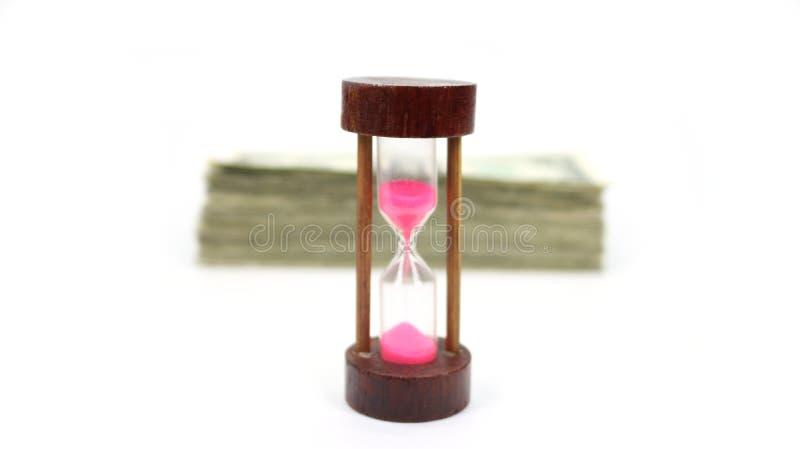 Le temps, c'est de l'argent avec la pile brouillée d'argent liquide derrière une minuterie en bois de sable vers le haut de Fro photo libre de droits