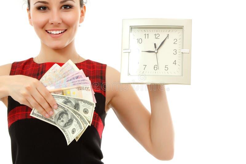 Le temps, c'est de l'argent - l'horloge se tenante gaie de femme d'affaires et encaissent dedans photos stock