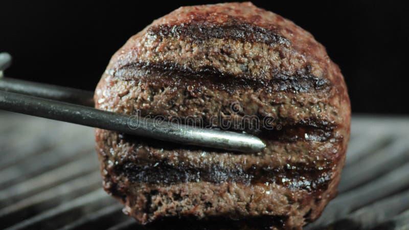 Le tenaglie del ferro hanno tenuto una cotoletta dal suo lato sulla griglia per la preparazione finale, fucilazione del primo pia immagini stock