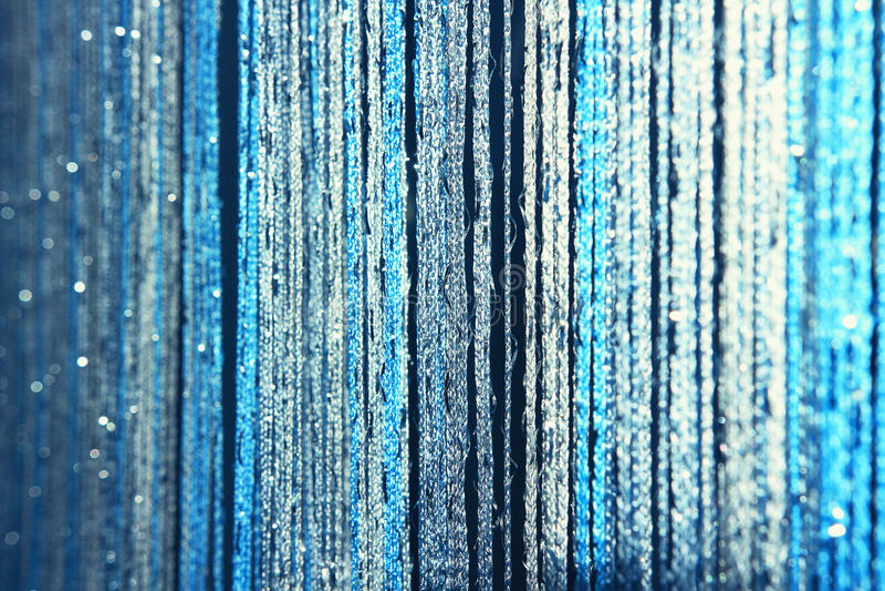 Le tende di struttura del fondo fatte del blu infila con scintillio e sfuocatura ai bordi fotografia stock