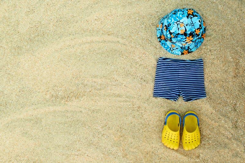 Le tenue de plage d'été de bébé, bascules électroniques, le chapeau, shorts sur le sable échouent images stock