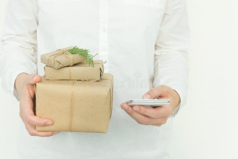 Le tenute della giovane donna in mani hanno impilato i contenitori di regalo di Natale in carta del mestiere con il ginepro e lo  immagini stock