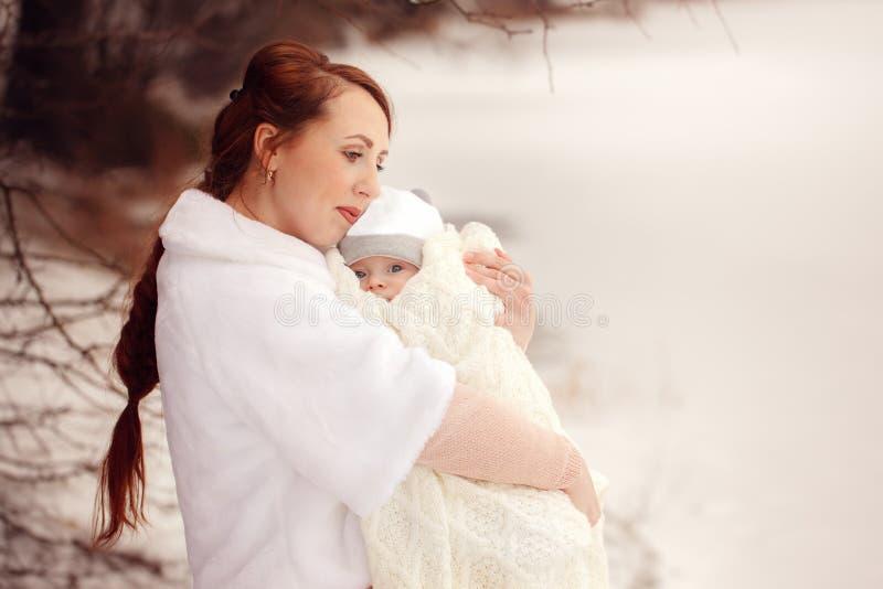 Le tenute della madre sulle mani il suo piccolo bambino sull'inverno camminano all'aperto fotografia stock libera da diritti