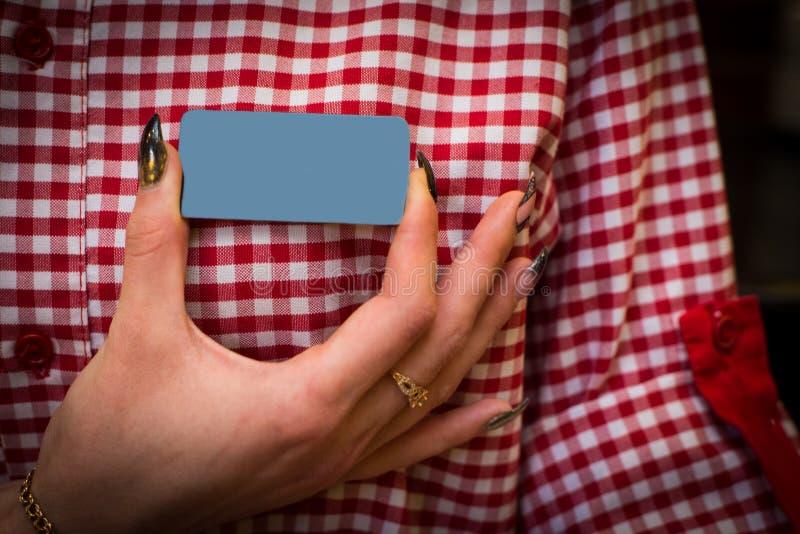 le tenute della mano soppressione il distintivo sulla camicia fotografia stock