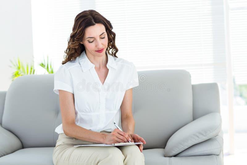 Le terapeuten som tar anmärkningar royaltyfria bilder