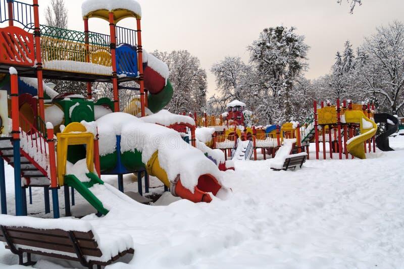 Le terrain de jeu coloré en hiver, regards a abandonné sous la neige photos libres de droits