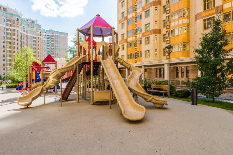 Le terrain de jeu des enfants modernes dans la maison de rapport de cour à Moscou photos libres de droits