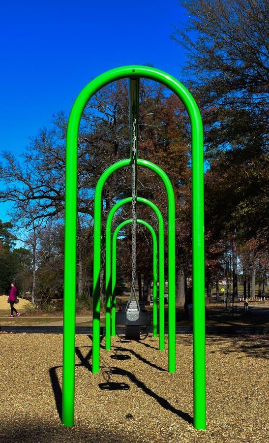 Le terrain de jeu vert clair balance au parc local photographie stock libre de droits