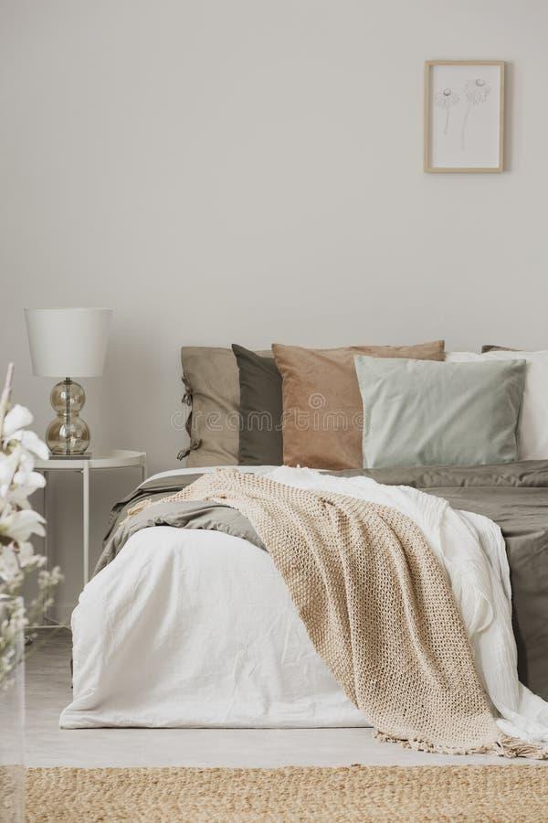Le terre coloranti nell'interno alla moda della camera da letto con re graduano il bedr secondo la misura fotografia stock libera da diritti