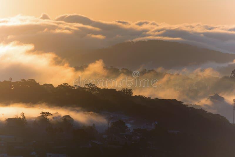 Le terre del plateau di Dalat della copertura della nebbia, Vietnam, fondo con magia della nebbia densa e del sole rays, il sole  fotografie stock