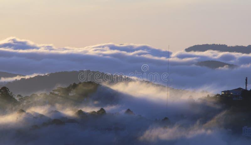Le terre del plateau di Dalat della copertura della nebbia, Vietnam, fondo con magia della nebbia densa e del sole rays, il sole  fotografia stock libera da diritti