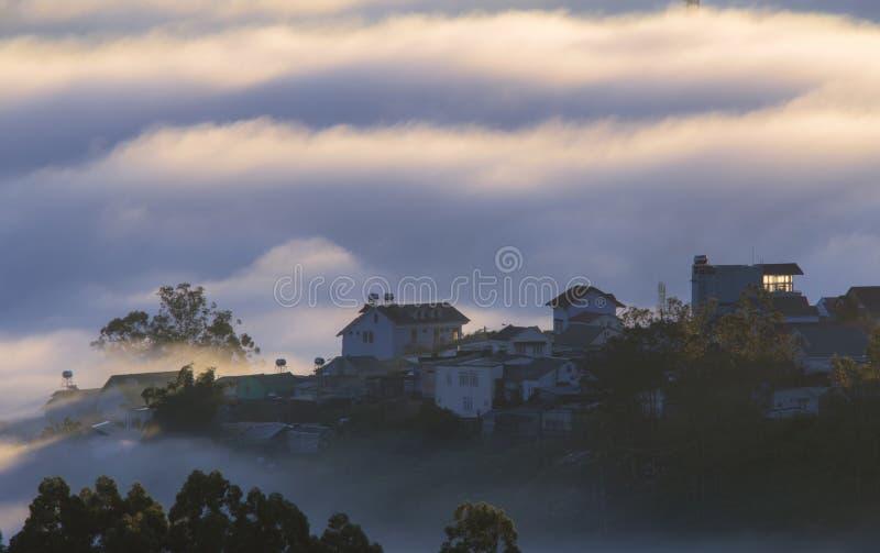 Le terre del plateau di Dalat della copertura della nebbia, Vietnam, fondo con magia della nebbia densa e del sole rays, il sole  immagini stock
