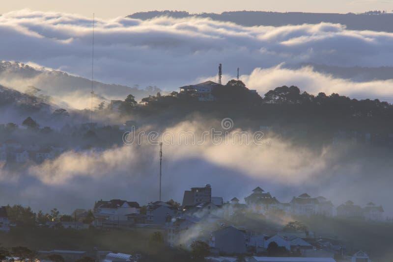 Le terre del plateau di Dalat della copertura della nebbia, Vietnam, fondo con magia della nebbia densa e del sole rays, il sole  immagine stock