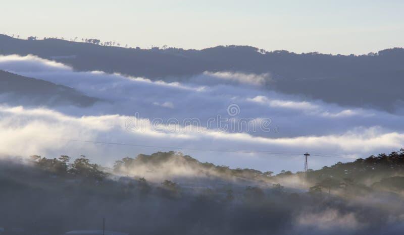 Le terre del plateau di Dalat della copertura della nebbia, Vietnam, fondo con magia della nebbia densa e del sole rays, il sole  fotografia stock