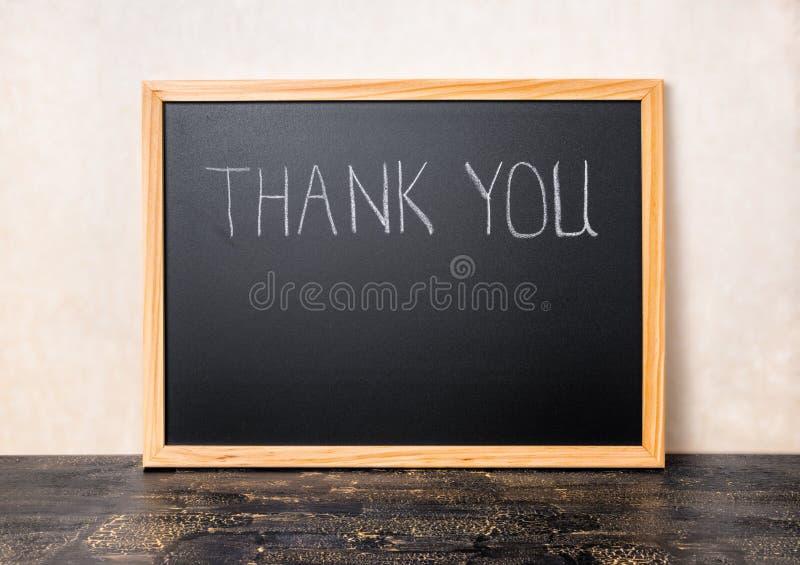 Le texte d'écriture vous remercient est écrit dans le tableau sur le craquelur photographie stock